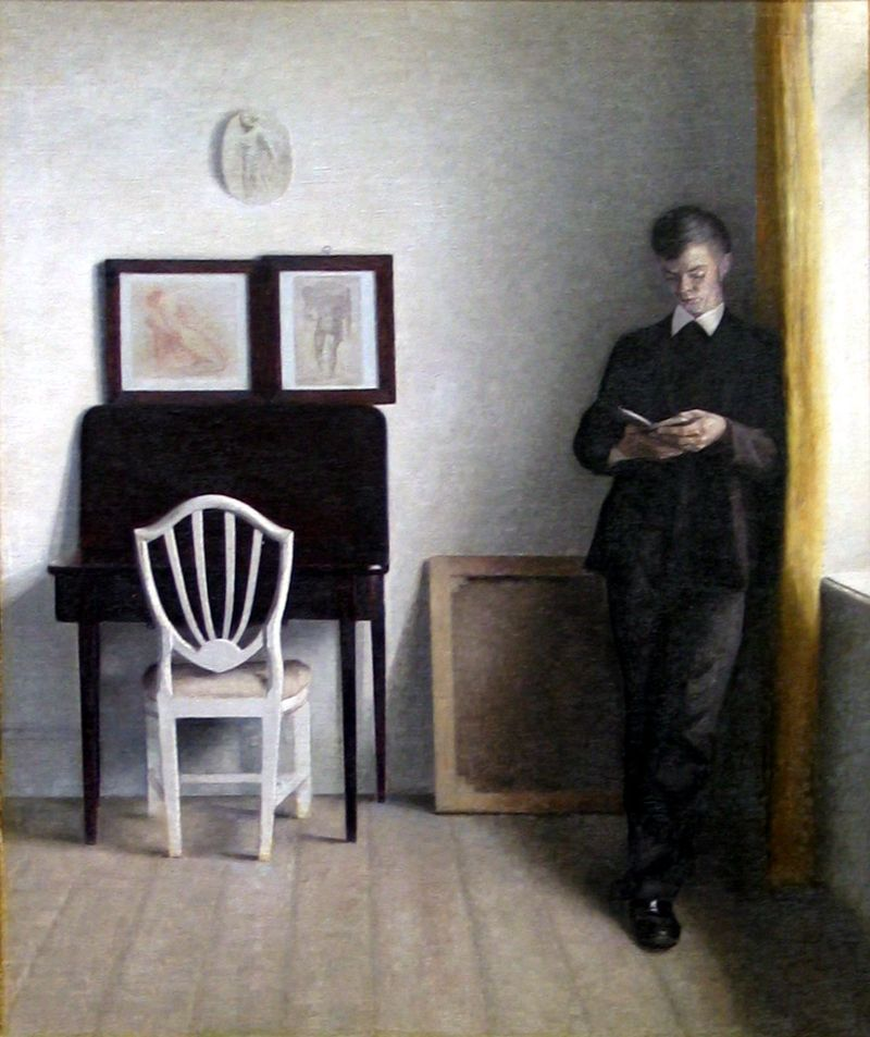 Interior with Young Man Reading by Vilhelm Hammershøi